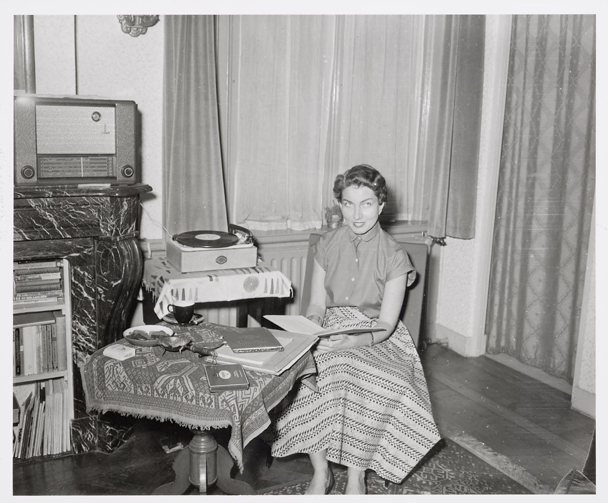 Interieur woning vrouw in kamer bij platenspeler for Interieur 1960