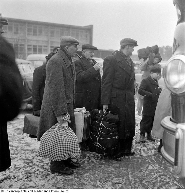 Evacués wachten bij bus op vervoer uit opvangcentrum Ossendrecht vlak na de watersnoodramp (1953)