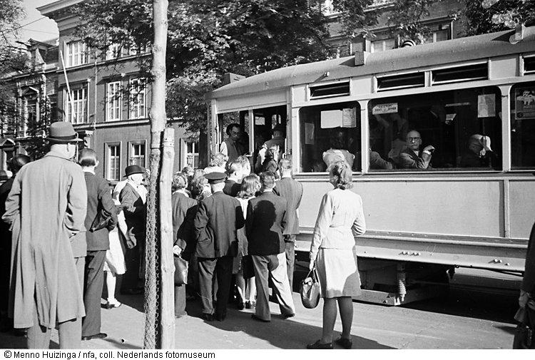 passagiers verdringen zich bij een tramhalte om in en uit een toch al overvolle tram te geraken. Black Bedroom Furniture Sets. Home Design Ideas