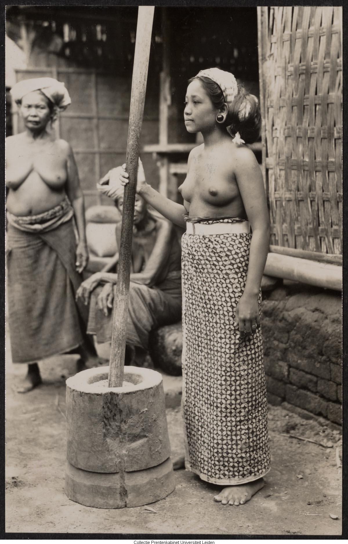 Drie vrouwen waarvan één bezig iets te malen