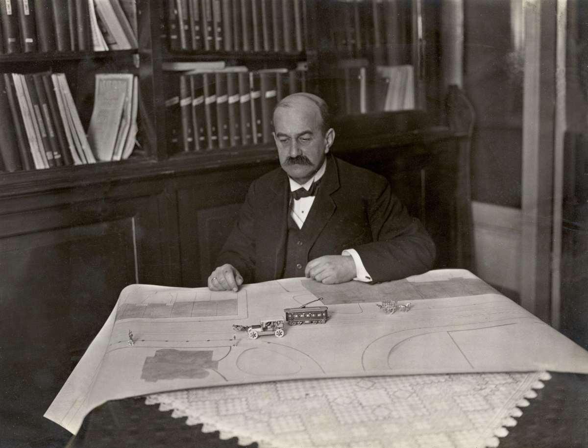 Autodeskundige ir. G.F. Steinbuch demonstreert voor de rechtbank met behulp van een plattegrond en miniatuurvoertuigen de wenselijkheid van het linkshouden door een auto bij een achterop komende tram, Amsterdam 1914.