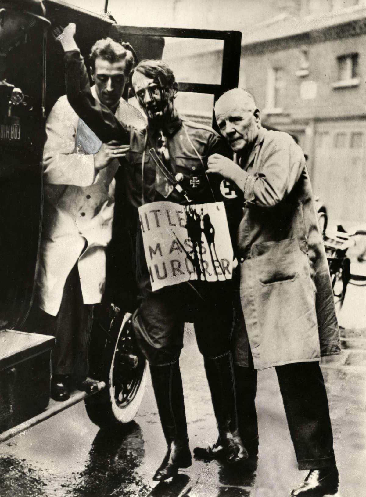 Aanloop naar de tweede wereldoorlog twee mannen tillen het besmeurde wassen beeld van adolf - Italiaanse douchegel ...