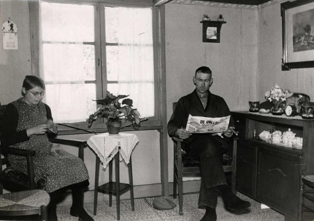 interieur boerenwoning vrouw stopt de sokken en man leest de krant rechts dressoir met serviesgoed plaats onbekend foto uit 1940