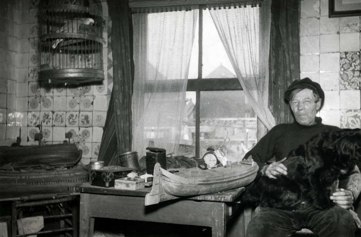 Oud Hollandse Tegeltjes : Scheepsmodelbouw. in zijn woning poseert een visser met de door hem