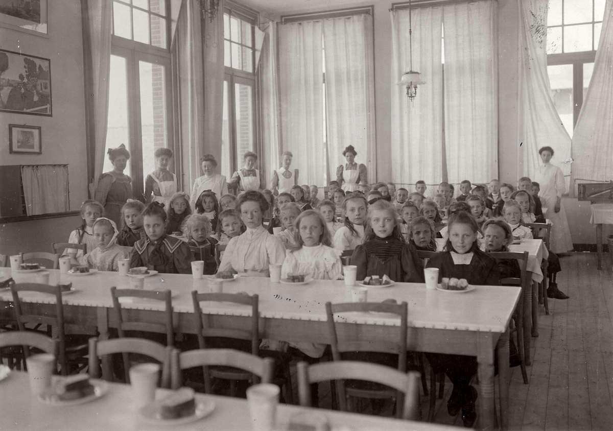 Kindertehuizen. Ontbijtzaal van het Centraal Genootschap voor kinderherstellings- en vakantiekolonies in Egmond aan Zee. Na aankomst krijgen de 'bleekneuesjes' een ontbijt geserveerd. Foto 1910.