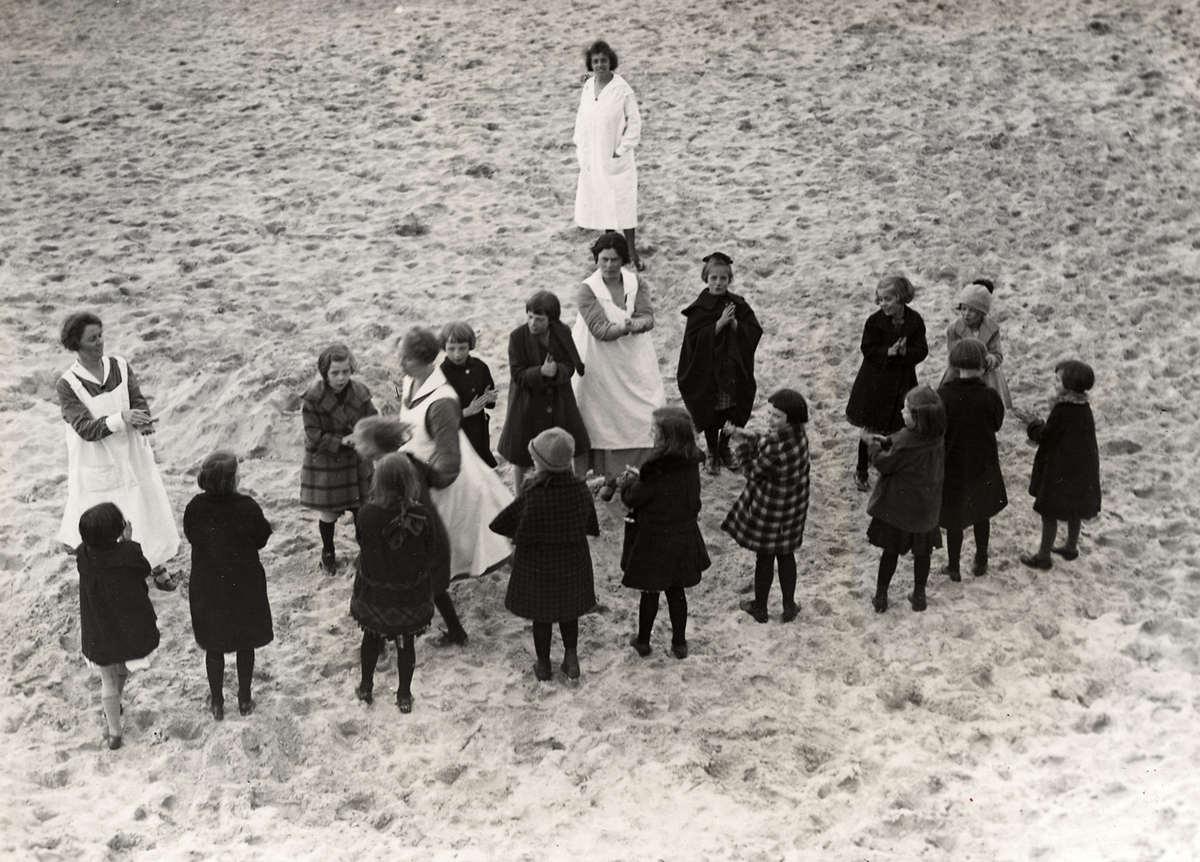 Kinderkolonie. In 1905 wordt in Egmond aan Zee door het Centraal Genootsdchap voor Kinderherstellings- en Vacantiekolonies het Kinderkoloniehuis Zwartedijk in Egmond aan Zee opgericht. Foto uit 1926: terwijl de directie toekijkt spelen de kinderen op het strand in Egmond aan Zee.