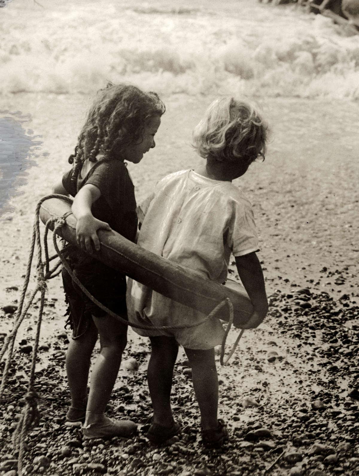 Twee kindjes in een reddingsboei op het strand plaats en land