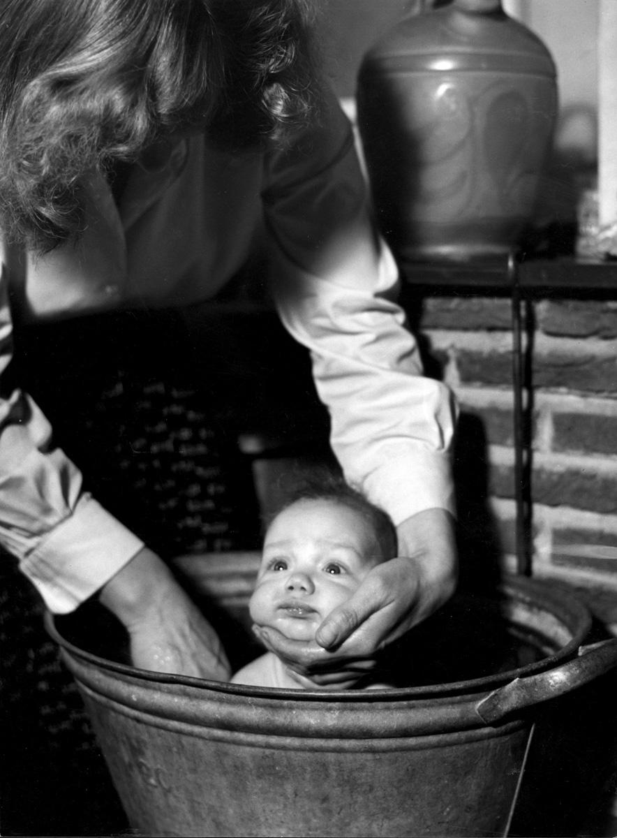 Moeder doet baby in een zinken teil in bad met een hand onder het hoofdje van het kind opdat - Foto in een bad ...