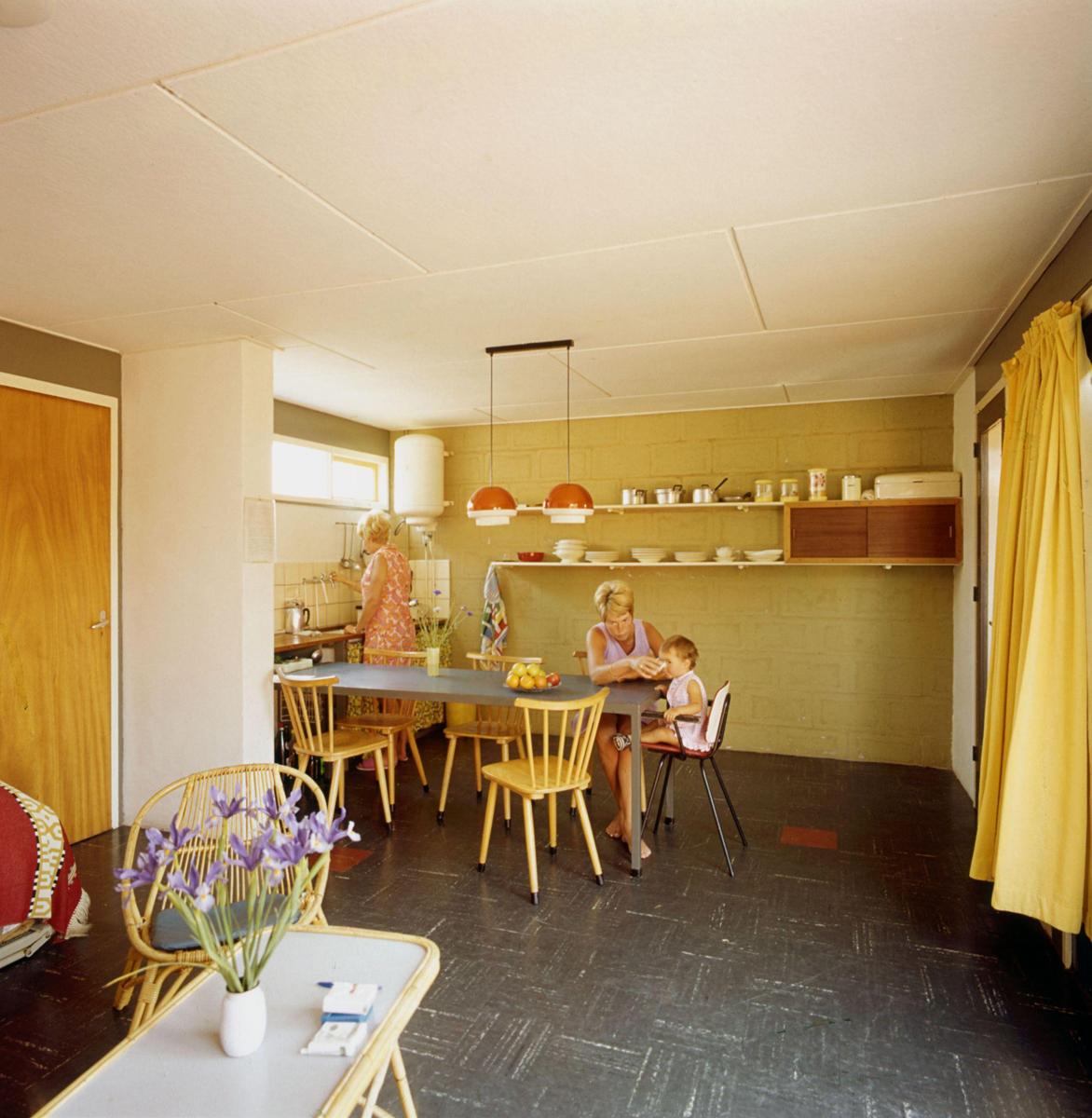 twee vrouwen en kind in vakantiehuisje jaren 60 70 interieur met rotan zitje colovinyl vloertegels en grote waterboiler in de keuken plaats onbekend