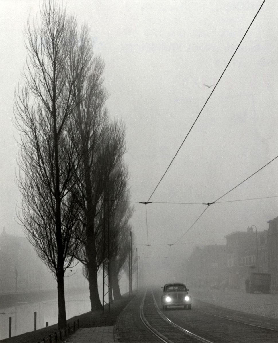 Auto (volkswagen kever) onder de tramleidingen in de mist, op de ...