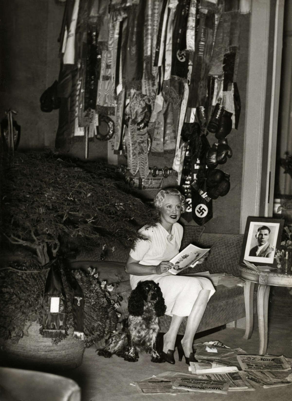 Voor de Teede Wereldoorlog. Mevrouw Max Schmeling - de actrice Annie Ondra - in 1936 in haar huis in Berlijn, temidden van de door Max Schmeling gewonnen medailles en erelinten (met hakenkruis!), na de overwinning van haar man op de Amerikaanse bokser Joe Louis. Duitsland. 1936.